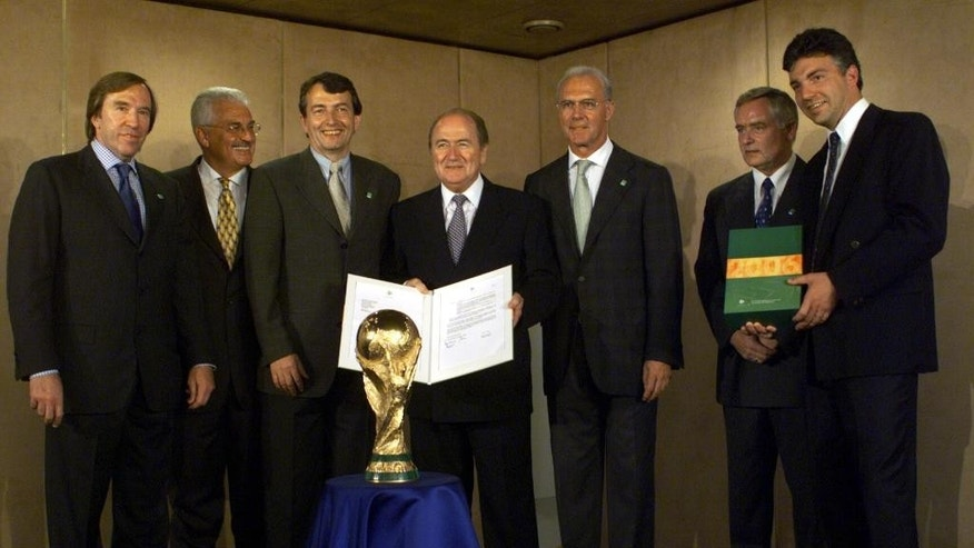 FILE - In this Aug. 10, 1999 file photo Guenter Netzer, Fedor Radmann, Wolfgang Niersbach, FIFA president Sepp Blatter, Franz Beckenbauer, head of the German bid committee, Horst R. Schmidt, secretary general of the German Football Association (DFB) and Michel Zen-Ruffinen, Fifa secretary general, from left, pose during the presentation of the 2006 FIFA World Cup Bid of Germany at the Fifa headquarters in Zurich, Switzerland.  (Christoph Ruckstuhl/Keystone via AP, file)