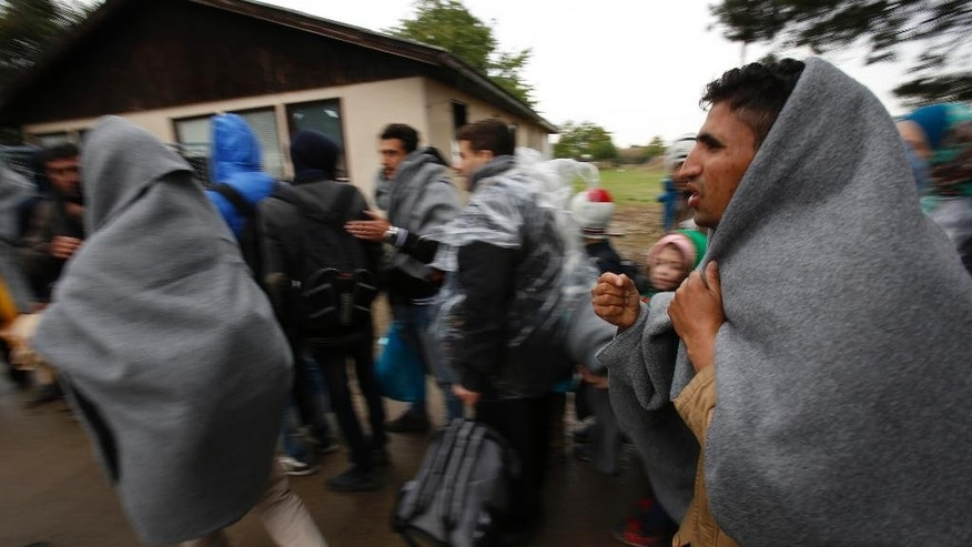 In this photo taken on Thursday, Oct. 15, 2015, people wrapped in blankets walk toward buses that will take them to Hungary from the admission center in Opatovac, Croatia. Volunteers on the Serbian side and government agencies on the Croatian side work day and night to make the autumn cold and rain more bearable for the tired and desperate. (AP Photo/Amel Emric)