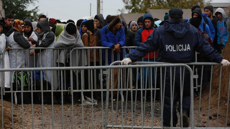 In this photo taken on Thursday, Oct. 15, 2015, migrants wrapped in blankets wait to board buses that will take them to Hungary from the admission center in Opatovac, Croatia. Aid workers say this short stretch between Serbia and Croatia has turned into a welcome center for the river of humanity passing through the Balkans. (AP Photo/Amel Emric)