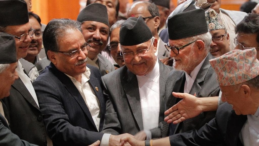 FILE - In this Sept. 16, 2015 file photo, Nepal's Prime Minister Sushil Koirala, center right, Communist Party of Nepal-Unified Marxist Leninist leader Khadga Prasad Oli, center, and Communist Party of Nepal (Maoist) Chairman Pushpa Kamal Dahal, center left, shake hands after the final constitution process at Constitution Assembly hall in Kathmandu, Nepal. After so many years of political deadlock and ever-lowering expectations and a churn of prime ministers who rarely survived a full year in office, Nepal has a new constitution. The main political parties in the Nepali plains, home to nearly half the population, boycotted the vote on the constitution, saying it gerrymanders districts to ensure the long-neglected plains people don't get too much power. (AP Photo/Niranjan Shrestha, File)