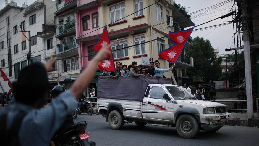 FILE - In this Sept. 27, 2015 file photo, students affiliated with the Communist Party of Nepal (Unified Marxist-Leninist), arrive near the Indian Embassy for a protest against the blockade of cargo trucks along the border with India in Kathmandu, Nepal. The main political parties in the Nepali plains, home to nearly half the population, boycotted the vote on Nepal's new constitution, saying it gerrymanders districts to ensure the long-neglected plains people don't get too much power. India, siding with the plains people and furious that their advice on the constitution had been ignored, effectively cut off fuel supplies to Nepal, creating lines at gas stations that seemed to stretch into eternity. (AP Photo/Niranjan Shrestha, File)