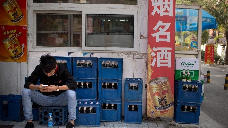 In this Thursday, Oct. 15, 2015 photo, a restaurant worker sits on crates of beer outside a convenience store as he uses his smartphone in Beijing. A potential prize for AB InBev in its bid for SABMiller is a Chinese beer, Snow, that is the world's biggest seller. But any deal will face Chinese regulators who have barred the two brewing giants in the past from cooperating. (AP Photo/Mark Schiefelbein)