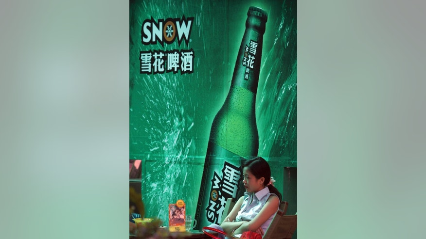 In this Sept. 11, 2006 photo, a woman sits near an advertising poster for Snow Beer in a bar in southwestern China's Chongqing municipality. A potential prize for AB InBev in its bid for SABMiller is a Chinese beer, Snow, that is the world's biggest seller. But any deal will face Chinese regulators who have barred the two brewing giants in the past from cooperating. (Chinatopix via AP) CHINA OUT