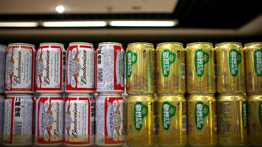 In this Thursday, Oct. 15, 2015 photo, cans of Budweiser beer, owned by AB InBev, sit next to cans of Snow beer, in which SABMiller has a 49 percent ownership stake, on a grocery store shelf in Beijing. A potential prize for AB InBev in its bid for SABMiller is a Chinese beer, Snow, that is the world's biggest seller. But any deal will face Chinese regulators who have barred the two brewing giants in the past from cooperating. (AP Photo/Mark Schiefelbein)
