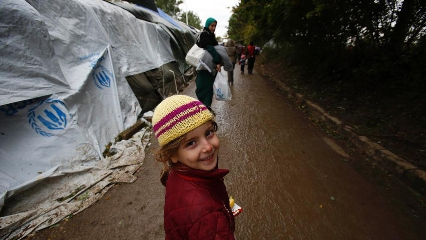 A migrant child smiles as she follows her mother down the path that leads to the Serbian-Croatian border crossing, at the village of Berkasovo, near Sid, Serbia, on Thursday, Oct.15, 2015. The migrants and refugees are struggling with the autumn rain and the cold as EU leaders are discussing in Brussels how to deal with the crisis. (AP Photo/Amel Emric)
