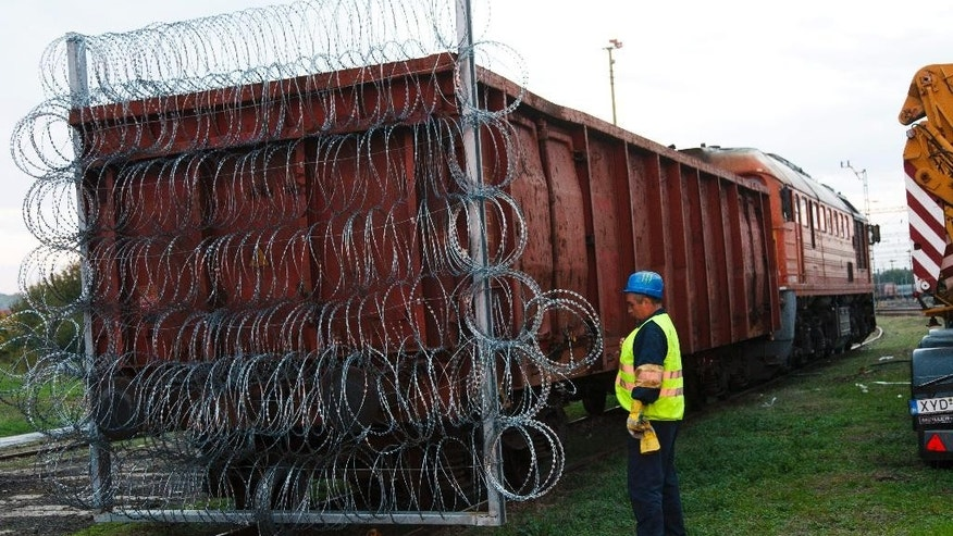 Razor wire is carried on a train wagon to be used as border closure between Hungary and Croatia, at the railway station in Zakany, 230 kms southwest of Budapest, Hungary, Friday, Oct. 16, 2015. Hungary clamped down on its border with Serbia with a barrier on Sept. 15 and says it will close down its border with Croatia to migrants starting at midnight. More than 383,000 migrants have entered Hungary this year, nearly all passing through on their way to Germany and other destinations farther west in the EU. (Gyorgy Varga/MTI via AP)