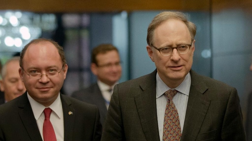 In this picture taken Thursday, Oct. 15, 2015, NATO Deputy Secretary-General Alexander Vershbow, right, walks with Romanian Foreign Minister Bogdan Aurescu, in Bucharest, Romania. Vershbow said Friday, Oct. 16, that Russia is more interested in shocking and intimidating rather than building a predictable relationship with the military alliance. (AP Photo/Vadim Ghirda)