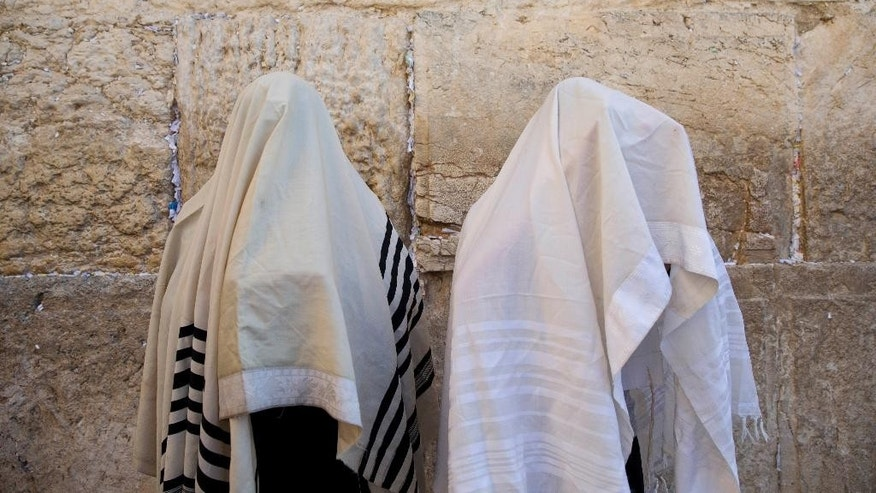 Jewish men pray at the Western Wall, the holiest site where Jews can pray in Jerusalem's Old City, Friday, Oct. 16, 2015. (AP Photo/Ariel Schalit)