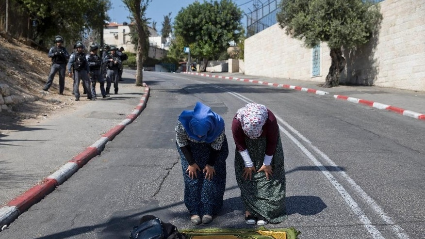 Two Palestinian women pray in the East Jerusalem neighborhood of Wadi Joz near Jerusalem's Old City during Friday prayers, Oct. 16, 2015. (AP Photo/Ariel Schalit)