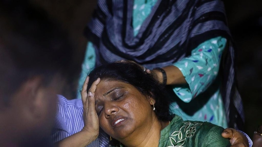 Mother of a victim of a fire is comforted by people outside a hospital in Mumbai, India, Friday, Oct. 16, 2015. Police say a cooking gas cylinder blast has killed less than a dozen people in a small hotel in Mumbai. (AP Photo/Rajanish Kakade)