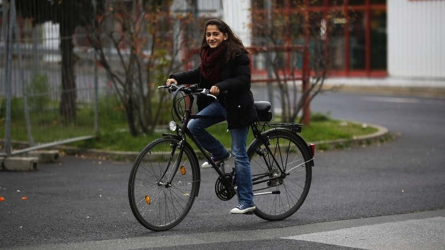 In this Tuesday, Oct. 13, 2015 photo Syrian refugee Raghad Habashieh tests a bicycle organized by German volunteers for her family outside the refugee camp in Heidenau, Germany. The camp, run by the German Red Cross, is located in the hall of a former DIY store. (AP Photo/Markus Schreiber)