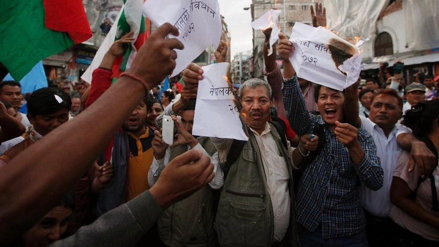 "FILE – In this Sept. 21,2015 file photo, Nepalese burn copies of the new constitution during a protest organized by splinter of the Maoist party, alliance of ethnic group and Madhesi party, in Kathmandu, Nepal. A New York-based human rights group has urged Nepal to investigate the dozens of deaths during protests by ethnic groups against the country's new constitution. Human Rights Watch said in a report released Friday, October 16, that at least 45 people have died in the protests that began in August and that the violence included ""extrajudicial killings by the police against protesters, killing of children and murders of police officers."" (AP Photo/Niranjan Shrestha, File)"