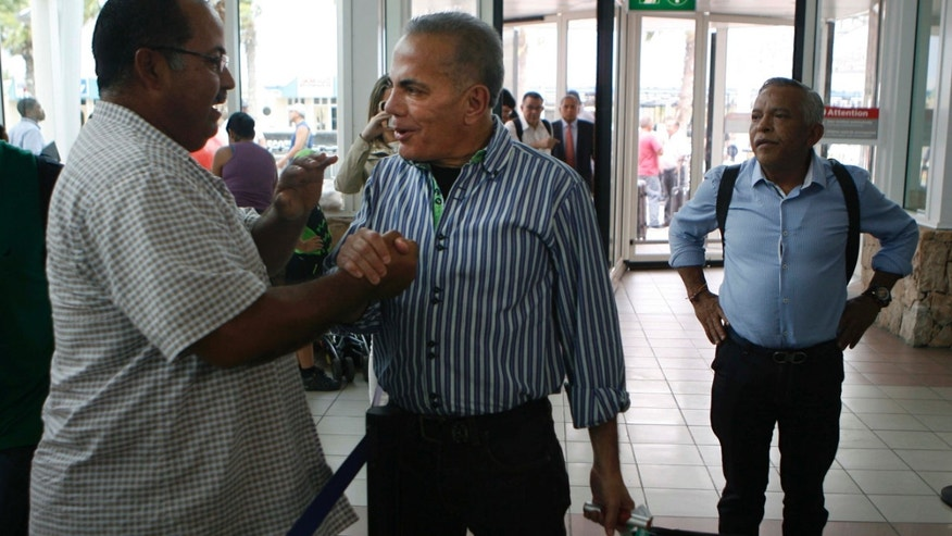 Oct. 15, 2015: A unidentified man shake hands with Venezuelan opposition leader Manuel Rosales, center, before he flies to Venezuela, at the airport near Oranjestad, Aruba.