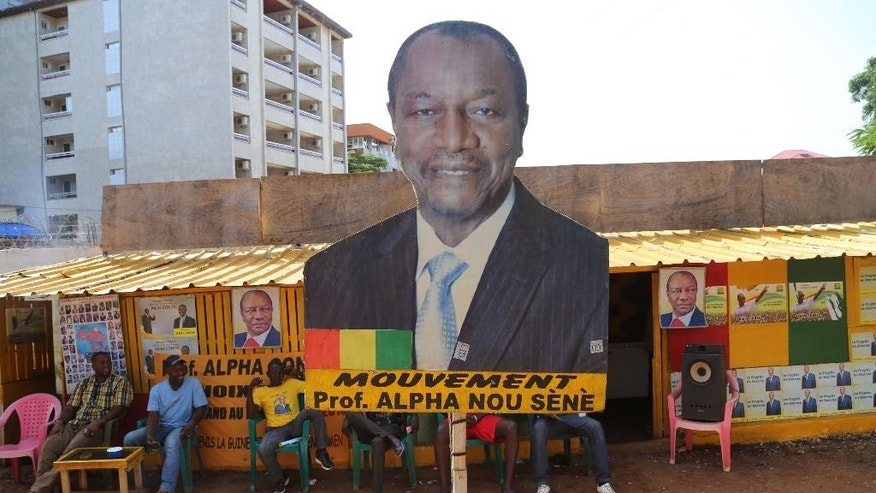 This photo taken Friday, Oct. 9, 2015, shows a billboard with the face of Guinea's incumbent President Alpha Conde in Conakry, Guinea. Guinea's President Alpha Conde could win another term in office after clinching a lead in partial results from Sunday's election, according to the election commission. (AP Photo/Youssouf Bah)