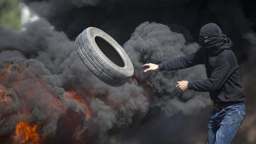 Palestinians burn tires during clashes with Israeli troops near Ramallah, West Bank, Friday, Oct. 16, 2015. Tensions and violence have been mounting in recent weeks, in part fueled by Palestinian fears that Israel is trying to expand its presence at a major Muslim-run shrine in Jerusalem, a claim Israel has denied.(AP Photo/Majdi Mohammed)