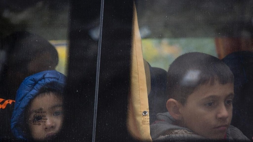 Children wait in a bus to be transferred to Austria, in Gruskovje, on the Croatian-Slovenian border, Saturday, Oct. 17, 2015. Hungary shut down its border with Croatia to the free flow of migrants, prompting Croatia to redirect thousands of people toward its border with Slovenia, (AP Photo/Darko Bandic)