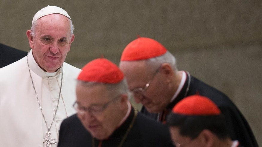 Pope Francis returns after a pause of a meeting marking the 50th anniversary of the creation of the Synod of Bishops, in the Paul VI hall at the Vatican, Saturday, Oct. 17, 2015. (AP Photo/Alessandra Tarantino)
