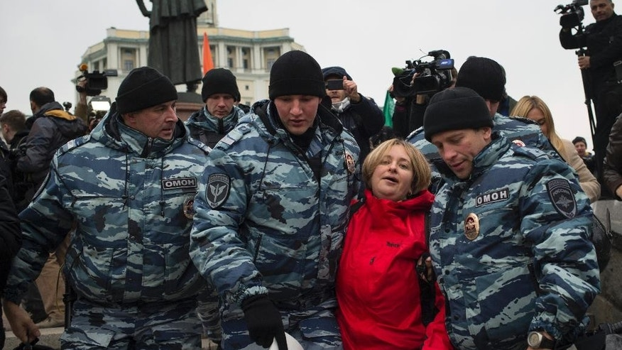 Police detain an anti-war protester in Moscow, Russia, Saturday, Oct. 17, 2015. Sanctioned anti-war in Ukraine and Syria protests were being held in downtown Moscow on Saturday. (AP Photo/Pavel Golovkin)