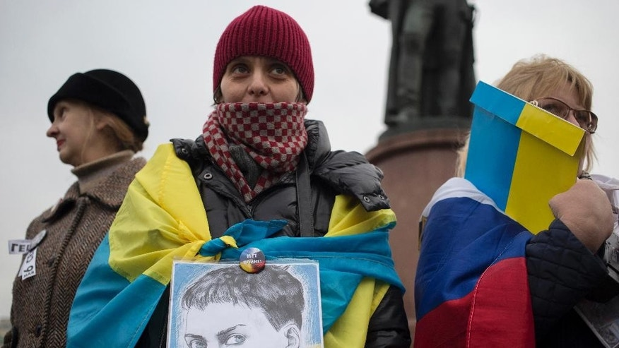 "A protester holds a portrait of Ukrainian military officer Nadezhda Savchenko, who is jailed in Russia, during an anti-war rally in Moscow, Russia, Saturday, Oct. 17, 2015. The pin reads ""No war"". Sanctioned anti-war in Ukraine and Syria protests were being held in downtown Moscow Saturday. (AP Photo/Pavel Golovkin)"