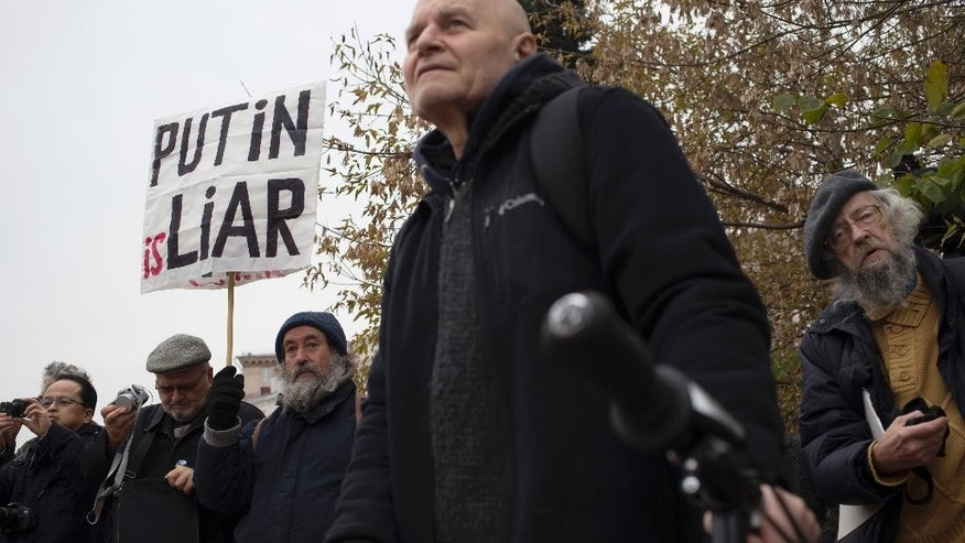 "A protester holds a banner during an anti-war rally in Moscow, Russia, Saturday, Oct. 17, 2015. Several hundred opponents of Russia's airstrikes in Syria have held a protest in Moscow. The demonstration on Saturday in a Moscow square near the Russian Army Theater attracted about 250 protesters, who held placards including one that called Syrian President Bashar Assad a murderer and added ""shame on Russia."" (AP Photo/Pavel Golovkin)"