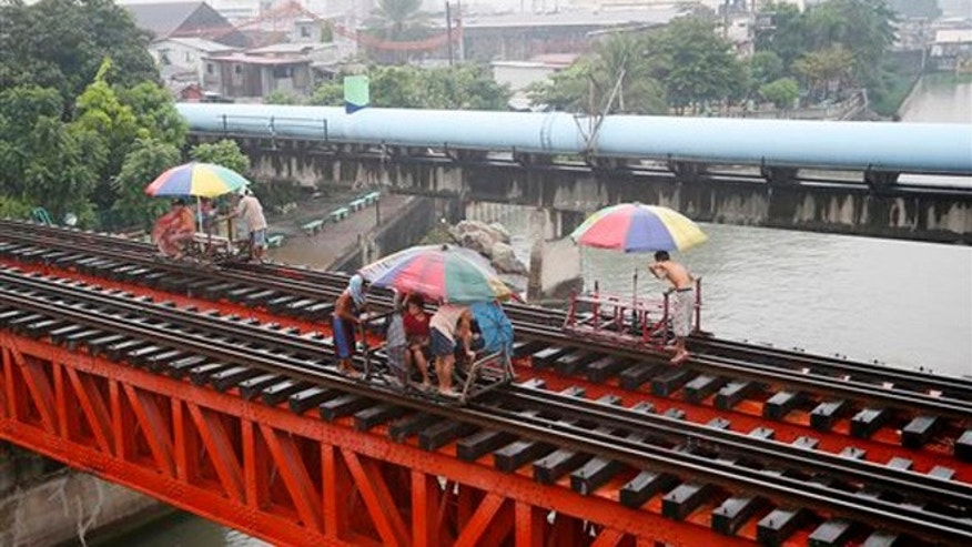"""Oct. 17, 2015: Commuters ride on a locally-built cart known as """"trolley"""" which makes use of a railroad track on a typhoon-induced rain in Manila, Philippines."""