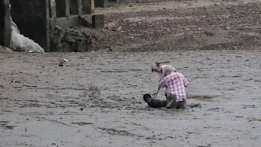 In this image made from video provided by Theerasak Saksritawee, Thai construction worker Chat Ubonchinda lies in the mud as he helps two unidentified Norwegian bird watchers who were sinking into a mudflat in Krabi, southern Thailand, Friday, Oct. 16, 2015. Chat lay down in the mud to allow the pair to use his body to pry themselves to safety. (Theerasak Saksritawee via AP) NO ARCHIVE, MANDATORY CREDIT
