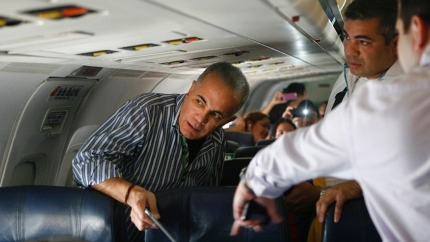 Venezuelan opposition leader Manuel Rosales, left, gets ready to leave a plane after it landed at La Chinita airport in Maracaibo, Venezuela, Thursday, Oct. 15, 2015. Rosales a former governor, who had been living in exile, was arrested when he returned to Venezuela and is expected to appear in a Caracas court later in the day. Rosales ran for president in 2006 and lost to Hugo Chavez. (AP Photo/Jhair Torres)