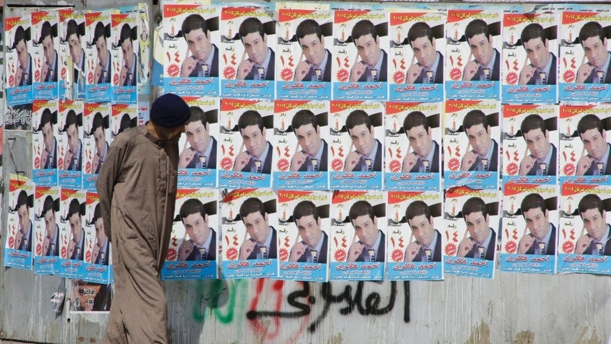 "An Egyptian walks in front of posters of a parliamentary candidate in Giza, just outside of Cairo, Egypt, Friday, Oct. 16, 2015. Egypt's long-awaited parliamentary elections will start on Oct. 18-19, a hoped-for step toward democracy amid a harsh crackdown on dissent. The second stage of the staggered vote will take place on Nov. 22-23. Final results will be announced in early December. Arabic reads, ""Ahmed Fekry."" (AP Photo/Amr Nabil)"