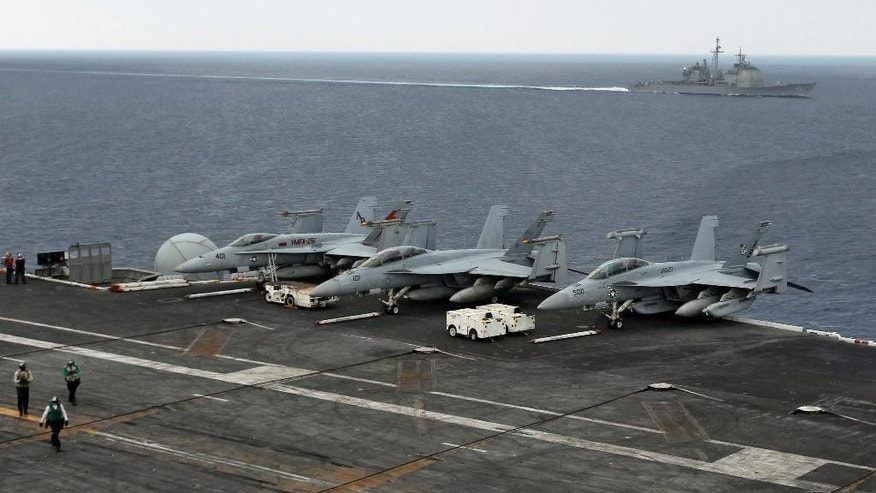 The USS Normandy sails in the Bay of Bengal as U.S. Navy fighter aircrafts are stationed at the flight deck of aircraft carrier USS Theodore Roosevelt (CVN 71) during Exercise Malabar 2015, some 152 miles off eastern coast of Chennai, India, Saturday, Oct. 17, 2015. Naval warships, aircraft carriers and submarines from the U.S., India and Japan are conducting joint military exercises off India's east coast, signaling the growing strategic ties between the three navies as they face up to a rising China. (AP Photo/Arun Sankar K.)