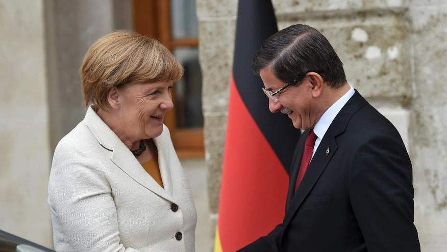Turkish Prime Minister Ahmet Davutoglu, right, greets Germany's Chancellor Angela Merkel, left, prior to their meeting at his office in Dolmabahce Palace in Istanbul, Sunday, Oct. 18, 2015. Merkel is meeting Turkish leaders to promote a EU plan that would offer aid and concessions to Turkey in exchange for measures to stem the mass movement of migrants across Europe's borders. (Bulent Kilic, Pool Photo via AP)