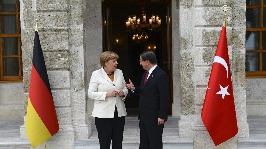 Turkish Prime Minister Ahmet Davutoglu, right,  talks toGermany's Chancellor Angela Merkel, left, prior to their meeting at his office in Dolmabahce Palace in Istanbul, Sunday, Oct. 18, 2015. Merkel is meeting Turkish leaders to promote a EU plan that would offer aid and concessions to Turkey in exchange for measures to stem the mass movement of migrants across Europe's borders. (Bulent Kilic, Pool Photo via AP)