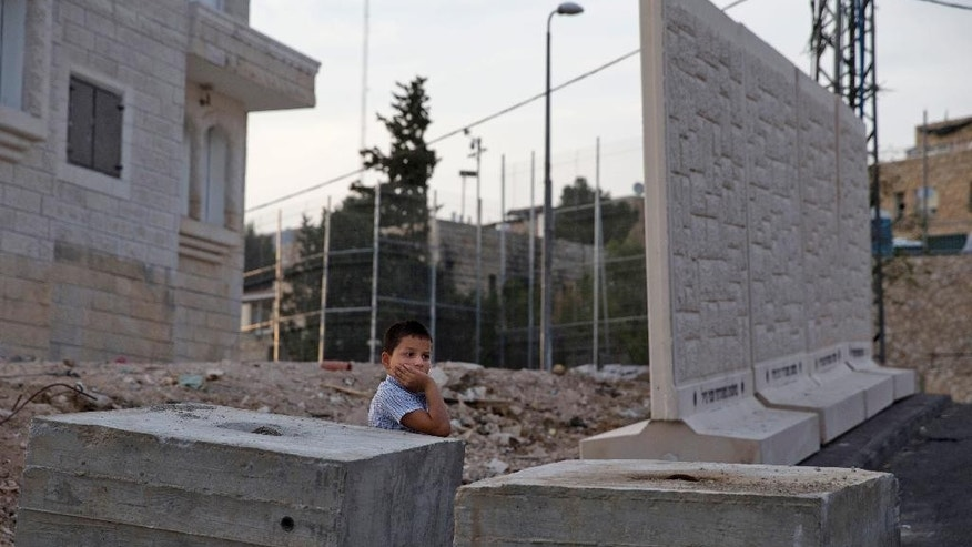 A Palestinian boy stands by concrete barrier between the Arab neighborhood of Jabal Mukaber and the Jewish area of Armon Hanatziv in east Jerusalem, Sunday, Oct. 18, 2015. Israeli police say they have set up a concrete barrier between a Jewish and an Arab neighborhood in east Jerusalem amid soaring tensions. Police spokeswoman Luba Samri says Sunday the slabs were placed there for security reasons, without elaborating. Rocks and firebombs have often been hurled from the Arab area at houses in the Jewish neighborhood. (AP Photo/Ariel Schalit)
