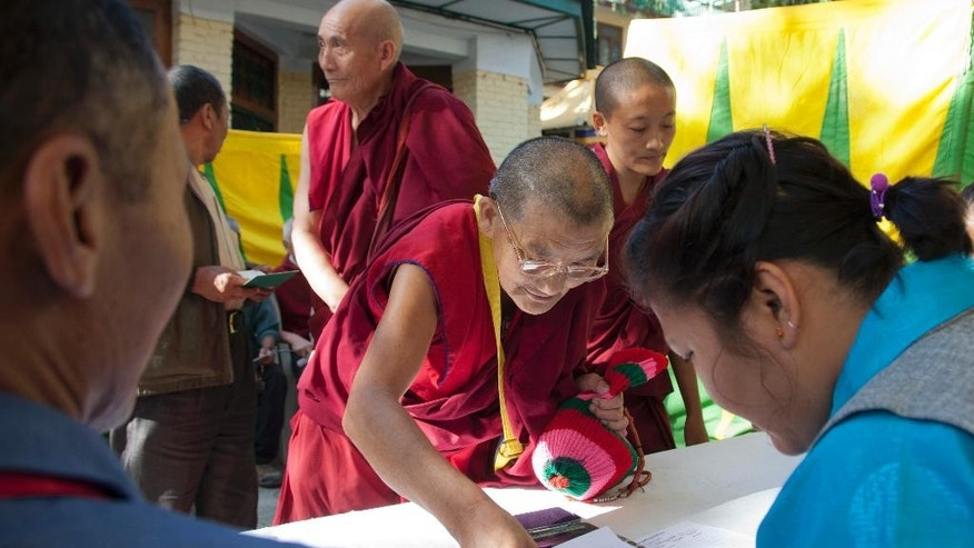 An exile Tibetan Buddhist nun puts her thumb impression as she registers herself before casting her vote in the first round of choosing a new government-in-exile in Dharmsala, where the exiled government is based, India, Sunday, Oct. 18, 2015. Tibetan communities worldwide are voting in the first round of choosing a new government-in-exile, and are debating how to carry on their campaign to free their Himalayan homeland from Chinese rule.(AP Photo/Ashwini Bhatia)