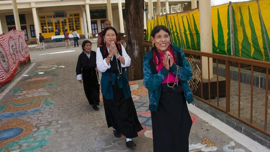 Exile Tibetans greet others as they arrive to cast their votes in the first round of choosing a new government-in-exile in Dharmsala, where the exiled government is based, India, Sunday, Oct. 18, 2015. Tibetan communities worldwide are voting in the first round of choosing a new government-in-exile, and are debating how to carry on their campaign to free their Himalayan homeland from Chinese rule.(AP Photo/Ashwini Bhatia)