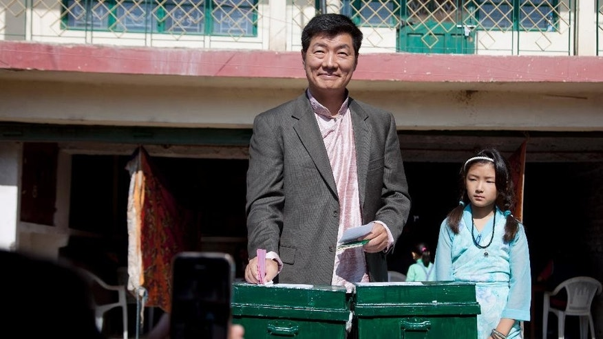 Lobsang Sangay, prime minister of the Tibetan government-in-exile, is accompanied by his daughter as he casts his vote in the first round of choosing a new government-in-exile in Dharmsala, where the exiled government is based, India, Sunday, Oct. 18, 2015. Tibetan communities worldwide are voting in the first round of choosing a new government-in-exile, and are debating how to carry on their campaign to free their Himalayan homeland from Chinese rule.(AP Photo/Ashwini Bhatia)