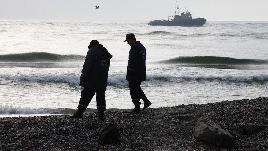 Ukrainian police officers investigate the coast near to where the boat Ivolga capsized on Saturday, Oct. 17, in a storm near the major port city of Odessa, Ukraine, Sunday, Oct. 18, 2015. The Ukrainian emergency services have blamed the accident on the overloading of the vessel, which was carrying 37 people, more than twice the maximum allowed of 15. (AP Photo/Sergei Poliakov)