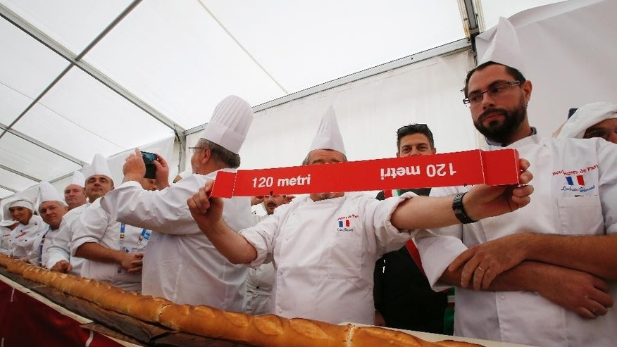 French and Italian bakers show a note reading 120 meters, at Expo 2015, in Rho, near Milan, Italy, Sunday, Oct. 18, 2015. A judge from the Guinness World Record Judge has certified a 122-meter -long (400-foot-long) baguette baked at the Milan Expo 2015 World's Fair as the longest in the world. The Italian maker of Nutella, Ferrero, backed the enterprise to beat the 111-meter record held by a French supermarket chain. (AP Photo/Antonio Calanni)