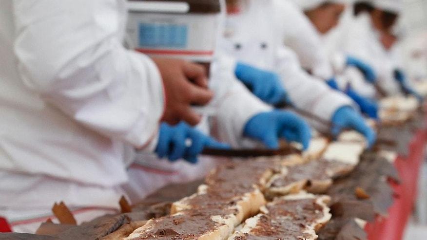 Bakers smear a record long baguette with Nutella at the Expo 2015 world's fair, in Rho, near Milan, Italy, Sunday, Oct. 18, 2015. A judge from Guinness World Records has certified a 122-meter -long (400-foot-long) baguette baked at the Milan Expo 2015 World's Fair as the longest in the world. The Italian maker of Nutella, Ferrero, backed the enterprise to beat the 111-meter record held by a French supermarket chain. (AP Photo/Antonio Calanni)