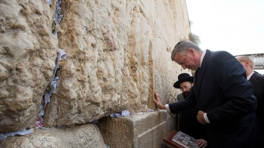 New York City's mayor, Bill De Blasio, touches the stones of the Western Wall, the holiest site where Jews can pray in Jerusalem's Old City, Sunday, Oct. 18, 2015. New York City's mayor, Bill De Blasio, on Saturday kicked off a brief visit to Israel that he has described as a solidarity mission at a difficult time. De Blasio is in the country after weeks of Israel-Palestinian violence. (AP Photo/Sebastian Scheiner)