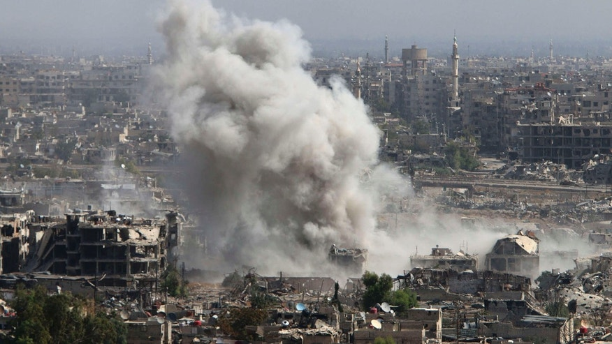 In this photo taken on Wednesday, Oct. 14, 2015, smoke rises after shelling by Syrian army in Jobar, Damascus, Syria.