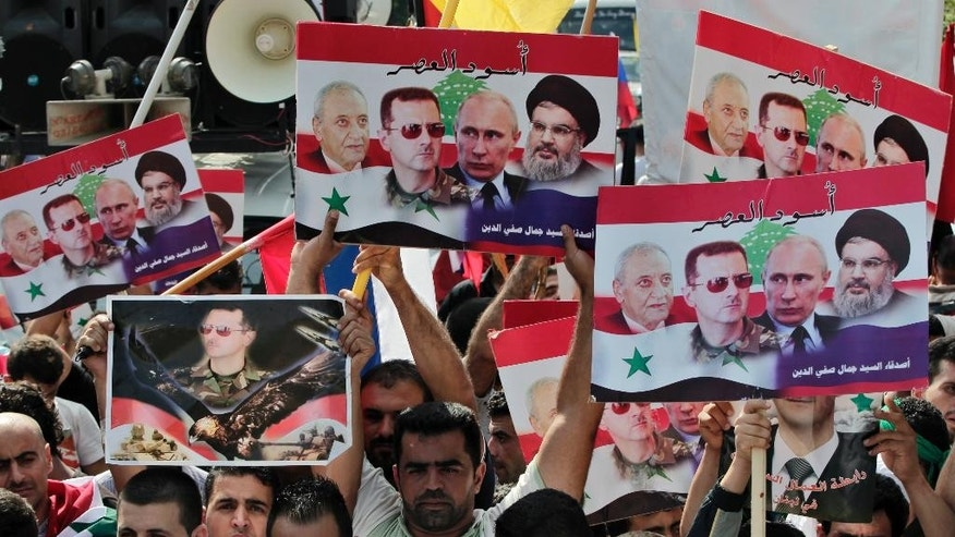 """Syrians who lives in Lebanon hold posters with photos of Syrian President Bashar Assad, Russian President Vladimir Putin, Hezbollah leader Sheikh Hassan Nasrallah, and Lebanese Parliament Speaker Nabih Berri, with Arabic that reads """"Lions of the time,"""" during a rally to thank Moscow for its intervention in Syria, in front of the Russian embassy in Beirut, Lebanon, Sunday, Oct. 18, 2015. (AP Photo/Bilal Hussein)"""