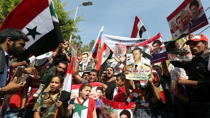 Syrians who live in Lebanon hold photos of Syrian President Bashar Assad, Russian President Vladimir Putin, Hezbollah leader Sheikh Hassan Nasrallah and Lebanese Parliament Speaker Nabih Berri, during a rally to thank Moscow for its intervention in Syria, in front of the Russian embassy in Beirut, Lebanon, Sunday, Oct. 18, 2015. (AP Photo/Bilal Hussein)