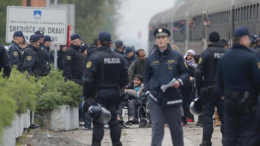Police officers organize groups of migrants after they arrive from Croatia in Sredisce ob Dravi, Slovenia, Sunday, Oct. 18, 2015.  Hungary shut down its border with Croatia to the free flow of migrants, prompting Croatia to redirect thousands of people toward its border with Slovenia. (AP Photo/Petr David Josek)
