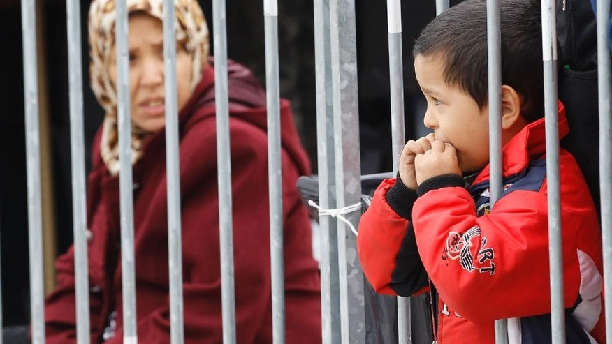 Young boy looks through bars as group of migrants waits to be registered after they arrive from Croatia in Sredisce ob Dravi, Slovenia, Sunday, Oct. 18, 2015. Hungary shut down its border with Croatia to the free flow of migrants, prompting Croatia to redirect thousands of people toward its border with Slovenia. (AP Photo/Petr David Josek)