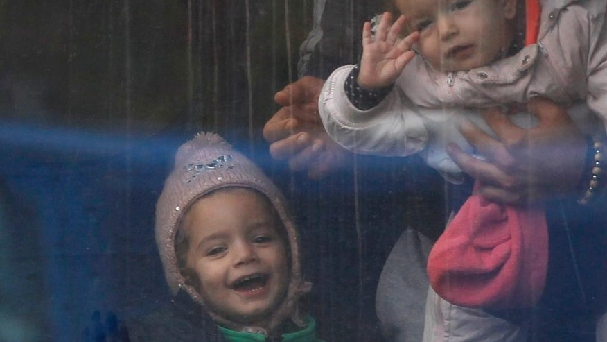 Young kids look out of a train window after they arrive from Croatia in Sredisce ob Dravi, Slovenia, Sunday, Oct. 18, 2015. Hungary shut down its border with Croatia to the free flow of migrants, prompting Croatia to redirect thousands of people toward its border with Slovenia. (AP Photo/Petr David Josek)