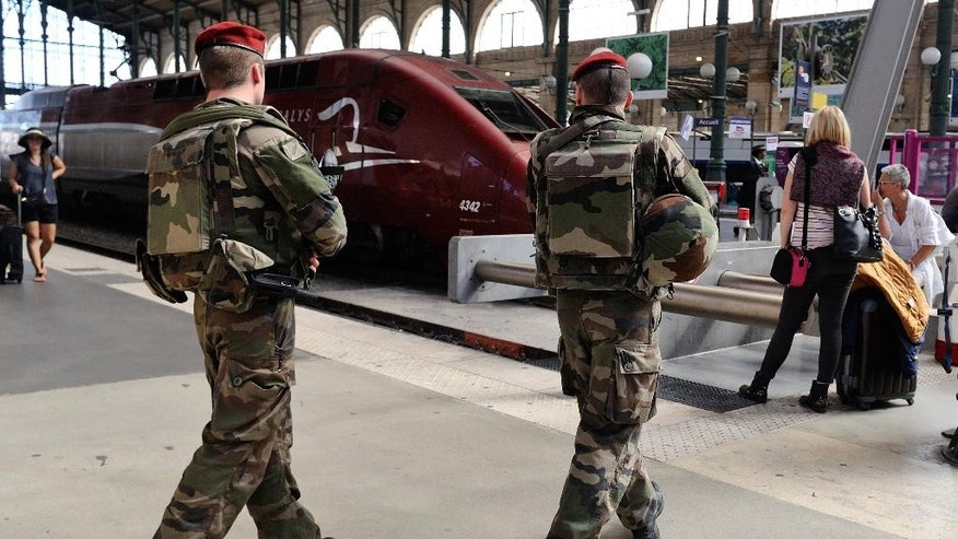 FILE - In this Aug. 22, 2015 file photo, French soldiers patrol at Gare du Nord train station in Paris, France.  France is tightening security on its vast public transit network after the attack on a high-speed Thalys train thwarted by a group of American friends. (AP Photo/Binta, File)