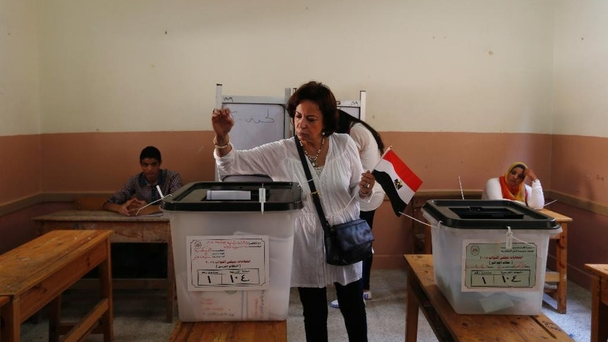 An Egyptian woman holds a national flag as she casts her vote during the first round of Egyptian parliamentary elections, at a polling station in Alexandria, Egypt, Sunday, Oct. 18, 2015. (AP Photo/Hassan Ammar)