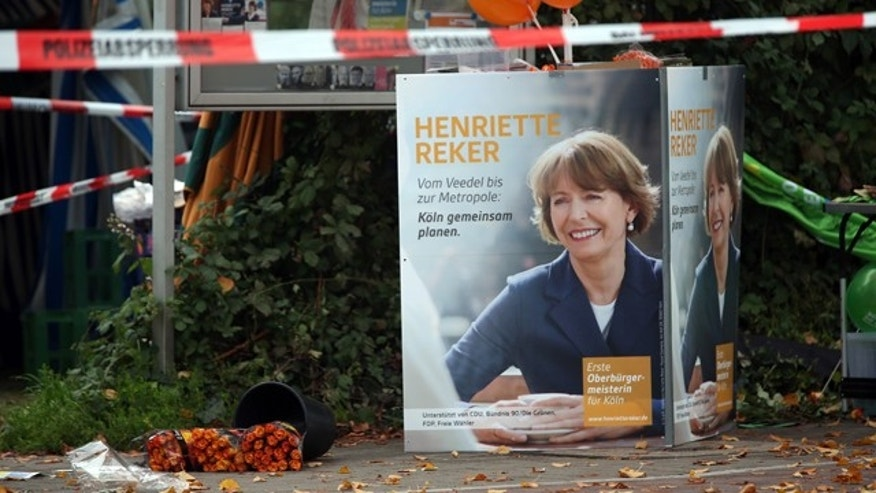 Oct. 17, 2015: Election posters of independent candidate for the mayor of Cologne Henriette Reker stand behind a police barrier in Cologne, Germany. Reker was wounded in a stabbing at this site as she campaigned on Saturday, a day before an election in the western German city. (Oliver Berg/dpa via AP)