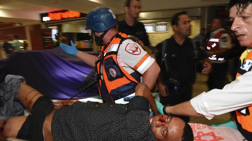 A wounded Eritrean is evacuated from the scene of an attack in Beersheba, Israel, Sunday, Oct. 18, 2015.  Israeli police said one Israeli was killed and several others were wounded in a shooting attack at a bus station in southern Israel, the attacker was also killed. Police commander Yoram Halevy said officers at the bus station mistakenly opened fire on the man during the attack Sunday, apparently thinking he was an assailant. ( AP Photo/Dudu Grunshpan)  ISRAEL OUT