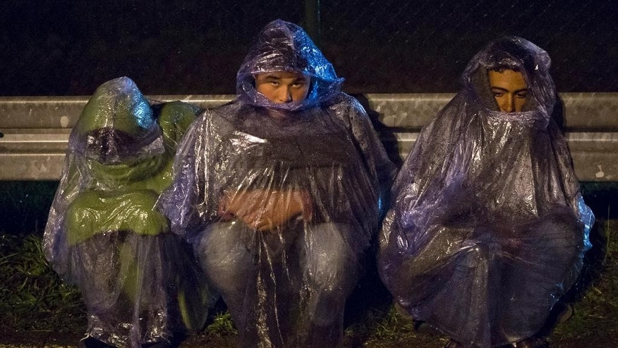 Migrants sit on the rain as they and hundreds of others are prevented to cross into Slovenia, at a border crossing with Croatia, in Sredisce ob Dravi, Slovenia early Monday, Oct. 19, 2015. Slovenia has said it will only take in 2,500 people a day, significantly stalling the movement of people as they fled their countries in the Middle East, Asia and Africa. (AP Photo/Darko Bandic)